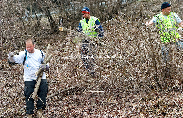 WATERBURY, CT. 22 March 2010-032210SV01--From left, Mike Hawley, Billy Torres, and Arjan Koda from the city of Waterbury help to clear brush from a hillside on Meadow Street by the exit 21 off ramp near I84 in Waterbury Monday. The crossover to Field street was closed for much of the day while the city workers cleand thearea with the help of a state tree crew.<br /> Steven Valenti Republican-American