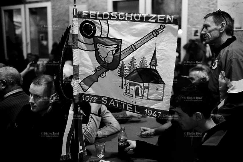 "Switzerland. Canton Zug. Morgarten. The group of men are members of the riflemen's association ""Felsdchützen Sattel"". On their flag are drawn a target, a saddle, a rifle and a christian church. The men wait for the results of the Morgartenschiessen (Morgarten shooting) competition. Thousands competitors from all over Switzerland came to fire fifteen shots at targets arranged on a meadow. The Battle of Morgarten occurred on 15 November 1315, when a 1,500-strong force from the Swiss Confederacy ambushed a group of Austrian soldiers of the Holy Roman Empire on the shores of Lake Ägeri near the Morgarten Pass. The Swiss, led by Werner Stauffacher, defeated the Austrians, who were under the command of Duke Leopold I. The Swiss victory consolidated the Everlasting League of the Three Forest Cantons, which formed the core of modern Switzerland. The victory of the Confederates left them in their virtual autonomy. Morgarten is a Swiss village which belongs to the municipality of Oberägeri in the canton of Zug. 15.11.2017 © 2017 Didier Ruef"
