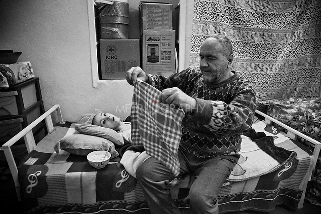 29.1.2015 Kirkuk, Iraq. Ganim Hormoz Gorgis 60 years old, prepares the usual meal of bread and milk for his boy Rony, 21, who has quadriplegia.