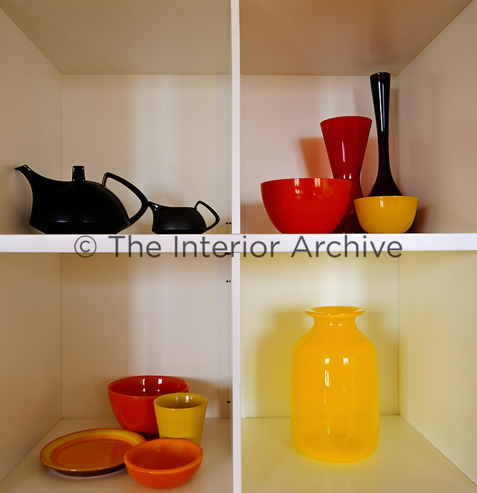 Detail of a collection of brightly coloured glassware and ceramics displayed in a shelving unit in the dining room