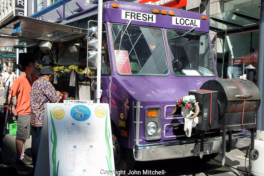 People ordering food at a food truck in downtown Vancouver, BC, Canada