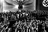 Hitler accepts the ovation of the Reichstag after announcing the &quot;peaceful&quot; acquisition of Austria.  It set the stage to annex the Czechoslovakian Sudetenland, largely inhabited by a German-speaking population.  Berlin, March 1938.  (OWI)<br /> Exact Date Shot Unknown<br /> NARA FILE #:  208-N-39843<br /> WAR &amp; CONFLICT BOOK #:  988