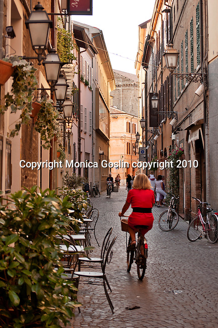 A woman wearing a red dress rides a bike down the streets of Ravenna, Italy.