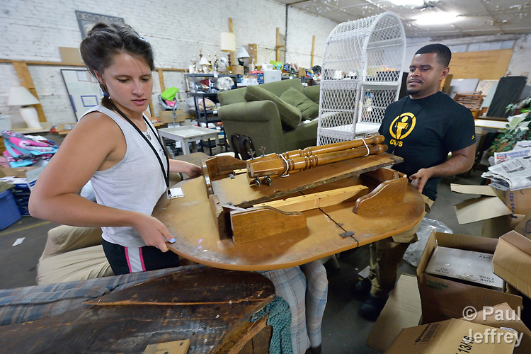 Emilie MacDonald and Luis Ortiz load furniture in a Church World Service warehouse in Lancaster, Pennsylvania. They are furnishing the apartment of a refugee family about to arrive in the United States.<br /> <br /> Photo by Paul Jeffrey for Church World Service.