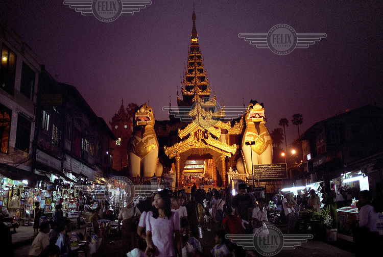 People stroll and shop on a street market in front of the entrance to the Shwedagon Pagod (also known as the Great Dagon Pagoda) in Rangoon (Yangon) at night time. ..