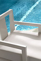 A pristine white armchair at the side of the hotel's indoor swimming pool