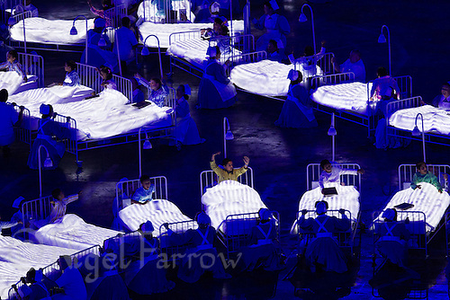 "27 JUL 2012 - LONDON, GBR - Nurses try to get children to go to sleep during the ""Second To The Right, And Straight On Till Morning"" section of the Opening Ceremony of the London 2012 Olympic Games in the Olympic Stadium in the Olympic Park, Stratford, London, Great Britain (PHOTO (C) 2012 NIGEL FARROW)"