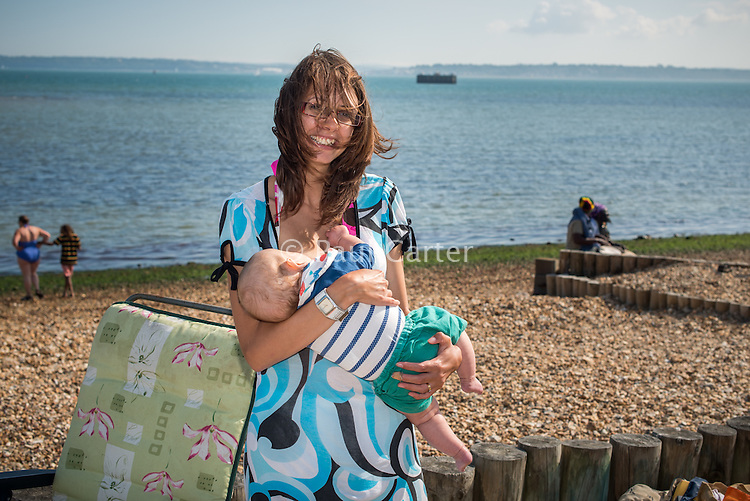 A young woman with wind blown hair breastfeeding her baby while standing up on a beach.<br /> <br /> Image from the breastfeeding collection of the &quot;We Do It In Public&quot; documentary photography picture library project: <br />  www.breastfeedinginpublic.co.uk<br /> <br /> <br /> Hampshire, England, UK<br /> 03 /09/2013<br /> <br /> &copy; Paul Carter / wdiip.co.uk