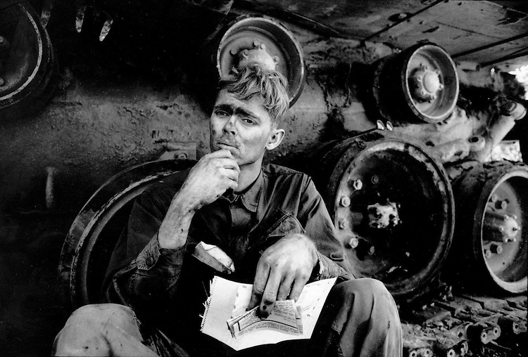 March, 1971   Lang Vei, Vietnam.A GI from an armoured battalion reads a letter from home while repairing a tank on Rt 9 in Lang Vei,  near Khe Sanh. He was supporting troops of the ARVN who had crossed into Laos to try and interdict supply lines from the NVA.  The soldier's name is TIMMONS (no first name available).  It is possible he was with the 1st of the 5th (autonomous Brigade, based in Quang Tri, VN). Picture taken approx. March 25, 1971.  .©2002 David Burnett/ Contact Press Images.[703] 527 2388 .No Reproduction Without Written Permission of the Photographer.