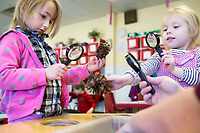 NWA Democrat-Gazette/CHARLIE KAIJO Sydney Holmes, 4 (from left) and Emily Wilson, 4, look at pinecones with magnifying glasses, Monday, February 12, 2018 at Helen R. Walton Children&acirc;&euro;&trade;s Enrichment Center in Bentonville. <br />