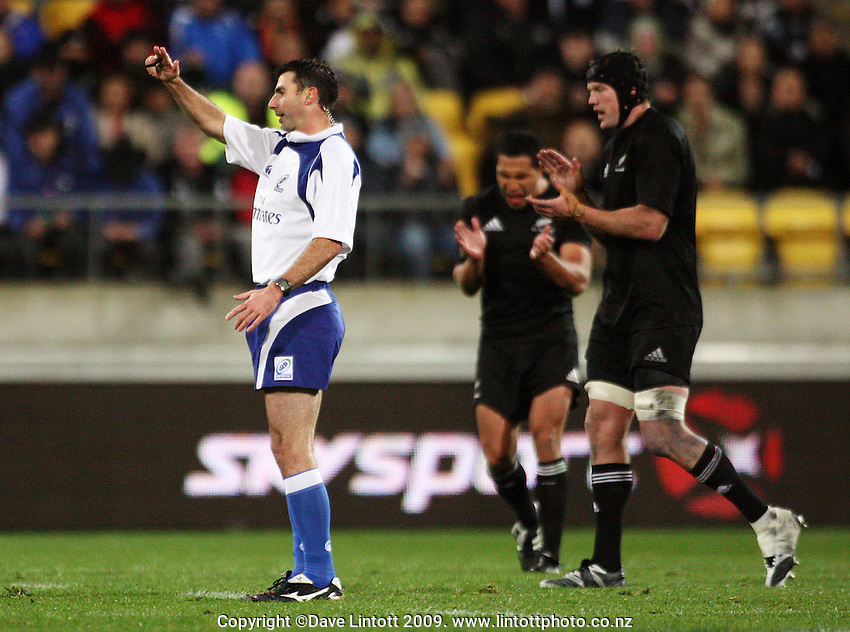 Referee Craig Joubert indicates the Wallabies have knocked the ball forward as Mils Muliaina and Tom Donnelly (right) celebrate during the Investec Tri-Nations match between All Blacks and Australia at Westpac Stadium, Wellington, New Zealand on Saturday 19 September 2009. Photo: Dave Lintott / lintottphoto.co.nz