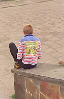 Boy age 14 sitting on stone railing.  Torun Poland