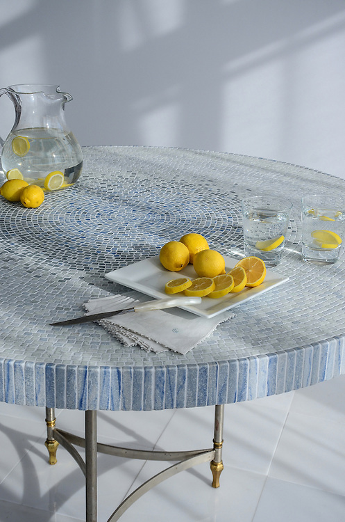This custom table by New Ravenna features Mist, a hand-chopped natural stone mosaic shown in tumbled Ming Green, Kays Green, Celeste, Calacatta, Blue Macauba and Lettuce Ming with Blue Macauba trim.<br />