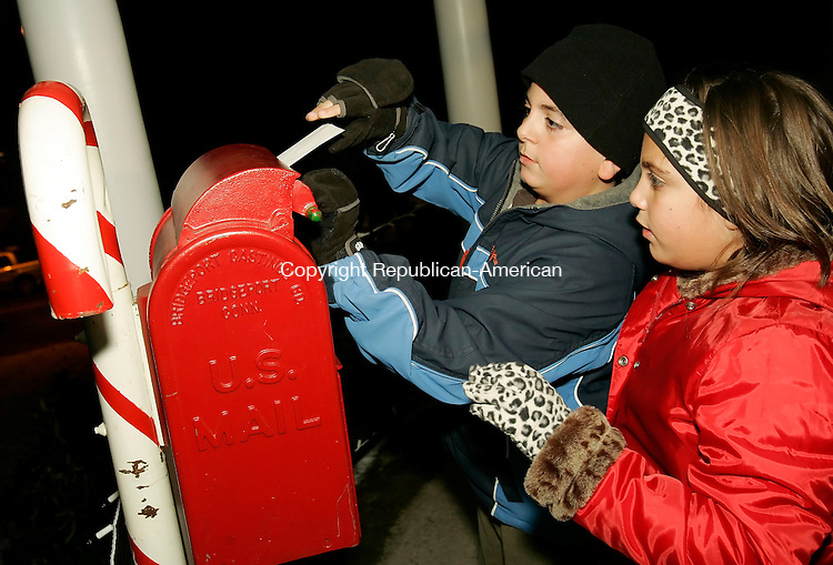WATERTOWN, CT 25 November 2005 -112505BZ01-  Thomas Ciarlo, 11, and Ashley Ciarlo, 9, of Watertown, drop their letters to Santa in a mailbox set up in the gazebo on the Veterans Hill Green in Watertown Friday night.  They were there to join in the &quot;Santa's Mailbox&quot; program which included a visit with Santa, music and refreshments.<br /> Jamison C. Bazinet Republican-American