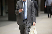 Man with a mobile phone outside Deutsche Bank, London Wall, City of London.