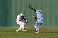 Center fielder Erik Samples (1), left, gives way to right fielder Tyler Lesch (2) of the University of South Carolina Upstate Spartans who catches a fly ball in a game against the UNC Asheville Bulldogs on Tuesday, March, 25, 2014, at Cleveland S. Harley Park in Spartanburg, South Carolina. (Tom Priddy/Four Seam Images)