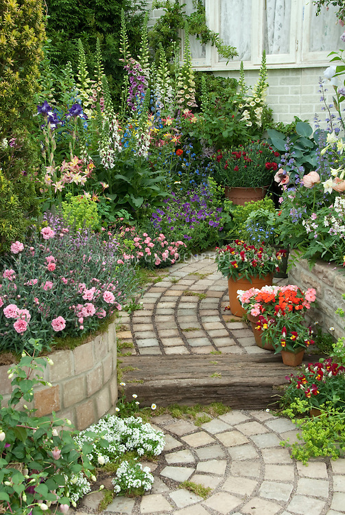 Stone garden path with lush flower garden plant flower for Parterre de fleurs zen