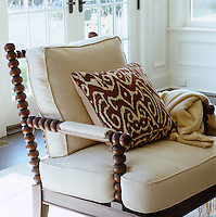 A comfortable armchair in the living room is upholstered in beige linen with a toning scatter cushion in an Ikat design