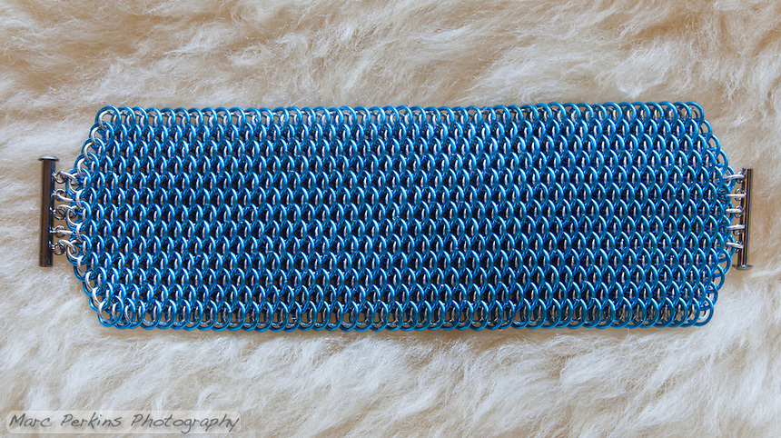 "A blue and silver dragonscale weave maille bracelet.  It's made from saw cut 18 gauge 1/4"" ID blue anodized aluminum rings and saw cut 19 gauge 5/32"" ID bright aluminum rings.  The clasp is a gunmental plated slide clasp.  The bracelet is on a sheepskin rug.  Handmade by Michelle."