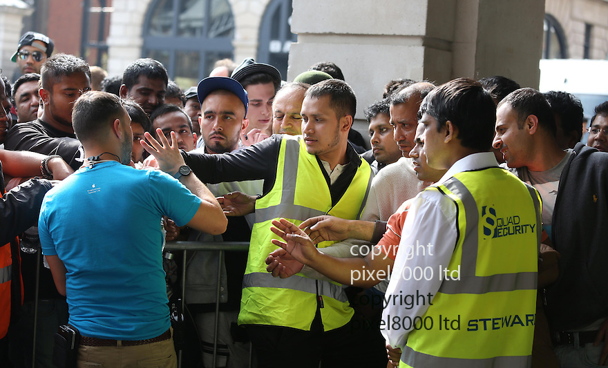 Pic shows: - <br /> Hundreds of iPhone lovers queue for new phone today at Apple Store in Covent Garden London.<br /> The majority were of asian or Indian appearance. Perhaps because the iPhone 6 is not launched there until later.<br /> There was quite a lot of pushing and shoving and dozens of yellow jacketed security staff were drafted in to help apple staff. Tempers got heated and times and the security had to step in to keep order.<br /> They also handed out water to keep tempers cool.<br /> <br /> <br /> <br /> <br /> Pic by Gavin Rodgers/Pixel 8000 Ltd