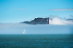 Sail Boat plying the San Francisco Bay in the fog with Golden Gate Bridge in the background