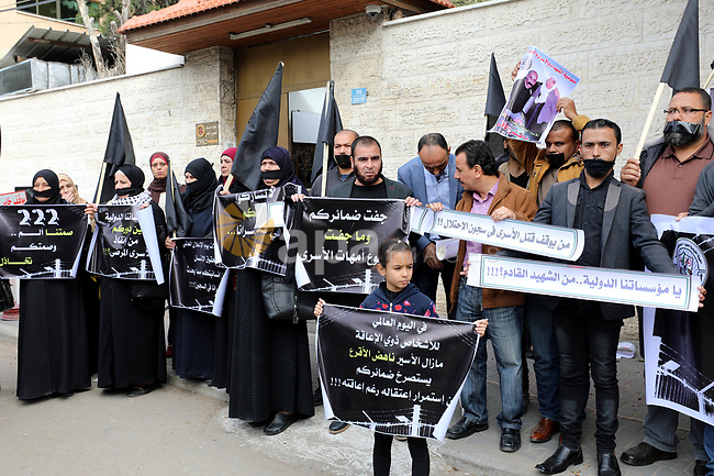 Palestinians take part in a protest in solidarity with prisoners in Israeli jails, in front of the Red Cross headquarters, in Gaza City, on December 4, 2019. Photo by Ramadan el-agha