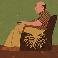 Man rooted to armchair holding remote control ExclusiveImage