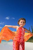 Enfant courant avec un paréo sur une plage de l'Ile des Pins, Nouvelle-Calédonie