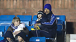 Manuel Pascali sits disconsolately in the family section cuddling his little boy after being sent off early in the game.