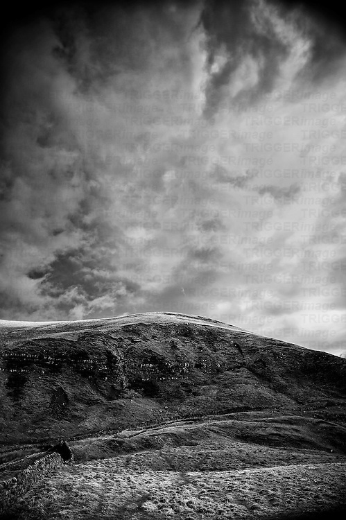 A magestic moody sky forms shadow & light patterns on a bleak hillside in the peak district.