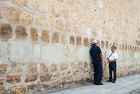 Two men chat outside of the walls of the Etno-botanical gardens of the Santo Domingo convent, Oaxaca City, Oaxaca, Mexico