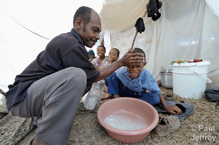 A boy's father washes his face in a camp for homeless families set up on a golf course in Port-au-Prince, Haiti, which was ravaged by a January 12 earthquake.