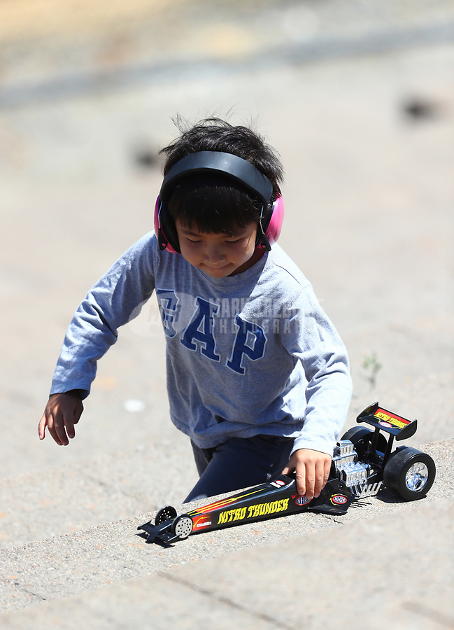 Jul 29, 2017; Sonoma, CA, USA; A young NHRA fan plays with a toy dragster during qualifying for the Sonoma Nationals at Sonoma Raceway. Mandatory Credit: Mark J. Rebilas-USA TODAY Sports