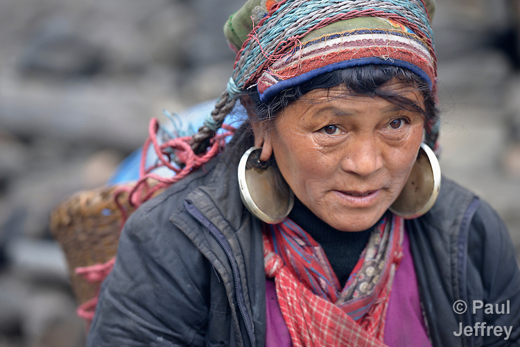 A woman carries a heavy load through the Tamang village of Goljung, in the Rasuwa District of Nepal near the country's border with Tibet.
