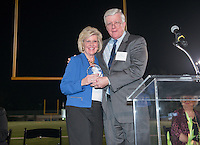 Mary (Dennis) Carpenter '63 accepts the Athletics Hall of Fame award for Roy Dennis '33 from James Dennis '66. Alumni, family, staff and students at the Occidental College Athletics Hall of Fame event, part of Homecoming weekend, Oct. 24, 2014 on Patterson Field. (Photo by Marc Campos, Occidental College Photographer)