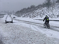 A lone cyclist on a snow covered road in Tredegar in south Wales, UK. Sunday 10 December 2017.