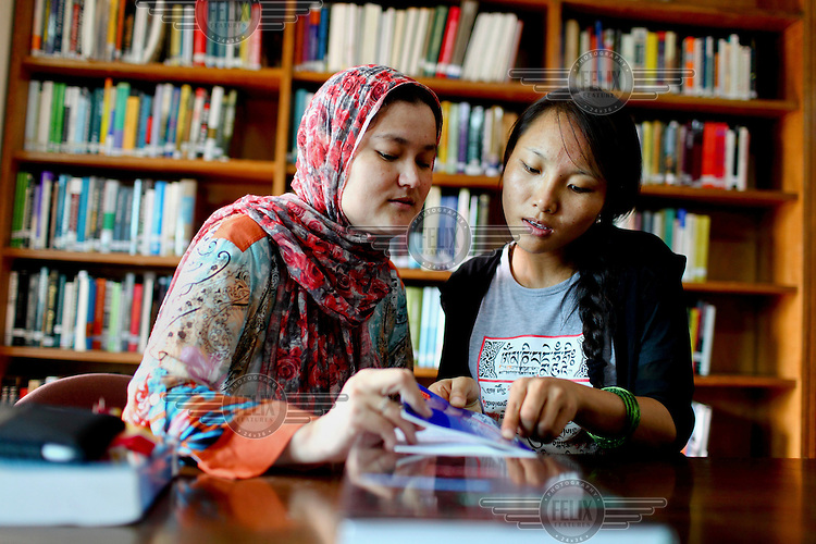 Yina from Tibet (right) and  Kubra Panzada (left)  from Afganistan study in the library at the Asian University for Women. /Felix Features