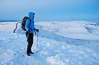 Single female hiker takes in winter view of Welsh landscape from summit of Pen Y Fan, Brecon Beacons national park, Wales