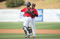 Kannapolis Intimidators relief pitcher Kelvis Valerio (26) gets a hug from catcher Brett Austin (20) after closing out the victory over the Lakewood BlueClaws at CMC-Northeast Stadium on May 17, 2015 in Kannapolis, North Carolina.  The Intimidators defeated the BlueClaws 4-1.  (Brian Westerholt/Four Seam Images)