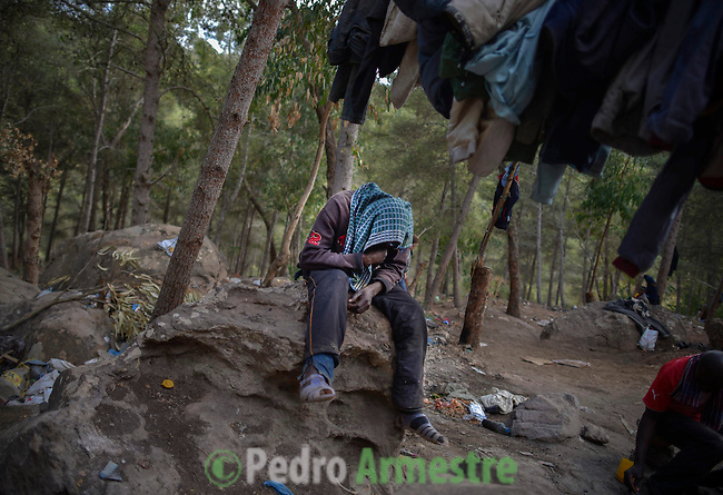 A sub-saharan immigrant  tries to rest in the mount Gurugú during the day of the Feast of the Sacrifice, Eid Kbir. October 26, 2012.Near 400 sub-Saharan immigrants survive in the mount Gurugú, in Morocco, waiting of an opportunity to jump the fence that separates them from Melilla, Spain, and from their dream of being employed at Europe. Many of them, between which there are minors, denounce violence from the police and the Moroccan army. © Pedro ARMESTRE