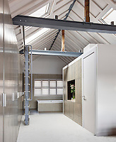 A modern bathroom in an industrial style room with a high pitched ceiling and exposed iron girders. A ladder allows access to Velux skylight windows. A window with louvre shutters is placed above a free-standing bath and a row of built-in cupboard provides plenty of storage.