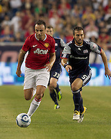 Manchester United FC forward Dimitar Berbatov (9) dribbles as New England Revolution defender A.J. Soares (5) closes. In a Herbalife World Football Challenge 2011 friendly match, Manchester United FC defeated the New England Revolution, 4-1, at Gillette Stadium on July 13, 2011.