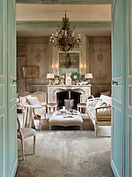 A pair of blue painted double doors open onto a formal sitting room with a central fireplace and, unusually, a concrete floor. A mirror hangs above an ornate fireplace.