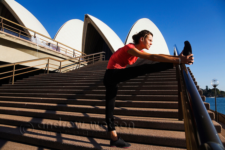 A female runner stretches on the steps of the Sydney Opera House. Sydney, New South Wales, AUSTRALIA.
