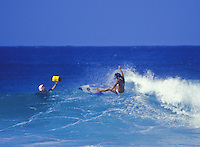 Woman surfer on a wave in clear blue water at Ehukai Beach, North Shore of Oahu