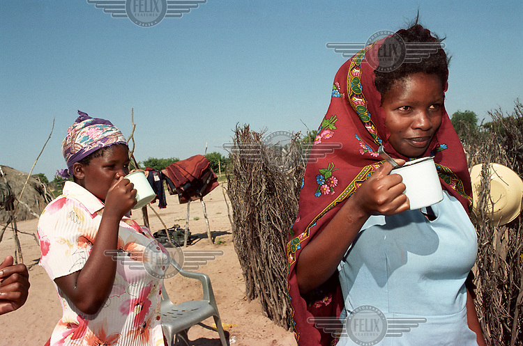 Women enjoy a cup of tea as Bushmen communities of the Central Kalahari Game Reserve prepare to return to their ancestral land after winning the court case against the Botswana government who illegally evicted them in 2002.