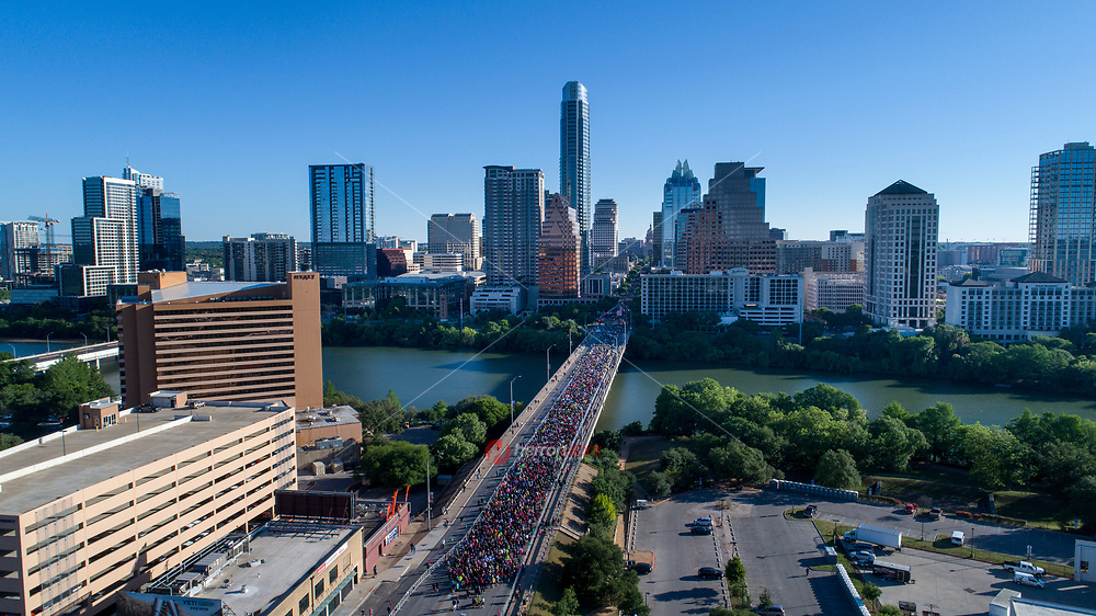 Birds eye aerial view as thousands of runners fill up the Congress Avenue Bridge during the Statesman Cap10K race in downtown Austin, Texas.
