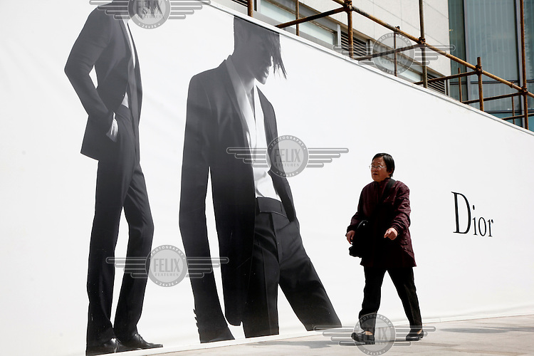 A woman walks past an advertisment billboard for the renowned French luxury goods brand Dior. Some local governments are instituting limits or banning outdoor advertisements for luxury brands, in hopes of curbing increasing public awareness of the widening wealth gap.