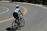 Caucasian female biking downhill on Flagstaff Mountain Road Boulder, Colorado. .  John leads private photo tours in Boulder and throughout Colorado. Year-round.