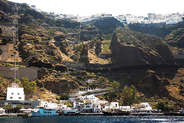 Skala Pier, or the Old Port of Santorini, with a donkey path and cable car, seen from the water sailing south in Santorini, Greece on July 5, 2013.